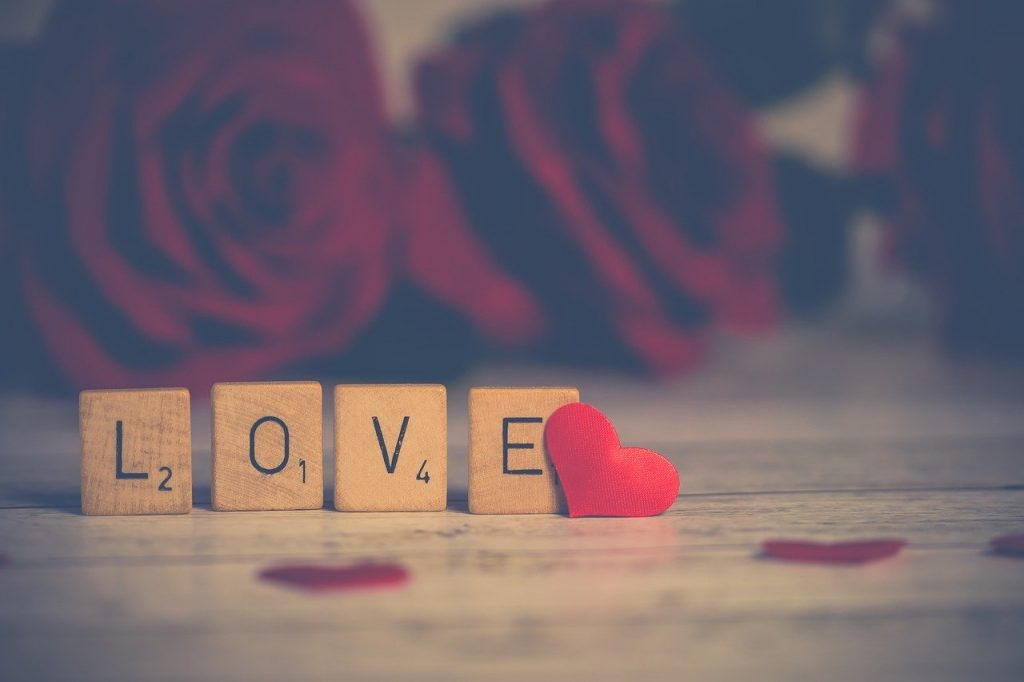Scrabble tiles spelling love and red roses